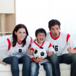 Stock Photo: Animated family watching football match