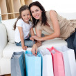Smiling mother and her daughter opening shopping bags — Stock Photo