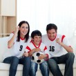 Lively famil ywatching football match - Stock Photo
