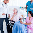 Stock Photo: Confident medical team taking care of senior woman