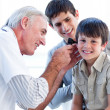 Senior doctor examining a little boy's ears — Stock Photo