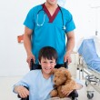 Portrait of a cute little boy sitting on wheelchair and a doctor — Stock Photo #10825995