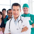Atractive doctor standing with his colleagues — Stock Photo