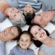 High angle of family lying on floor with heads together — Stock Photo