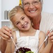 Happy grandmother eating a salad with granddaughter — Stock Photo