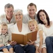 Grandmother reading a book to her children and parents — Stock Photo