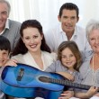 Portrait of family holding a guitar in living-room — Stock Photo #10826126