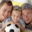 Portrait of smiling son, father and grandfather on floor - Stockfoto