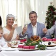 Family tusting in a Christmas dinner with white wine — Stock Photo #10826153