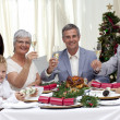 Family tusting in a Christmas dinner with white wine — Stock Photo