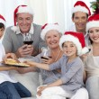 Family drinking wine and eating sweets in Christmas — Stock Photo #10826176