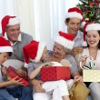 Family opening Christmas presents at home — Stock Photo