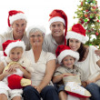 Children sitting with their family holding Christmas boots — Stock Photo #10826193