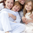 Portrait of young family lying in bed — Stock Photo
