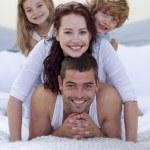 Portrait of happy family having fun in bed — Stock Photo
