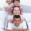 Happy family playing in bed together — Foto de stock #10826220