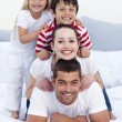 Foto Stock: Happy family playing in bed together
