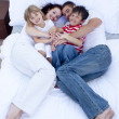 Stock Photo: High view of parents and children relaxing in bed