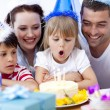 Little girl blowing out candles in her birthday — Stock Photo #10826226