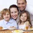Stock Photo: Children having breakfast with their parents