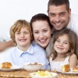 Portrait of happy family having breakfast — Stock Photo