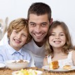 Portrait of children having breakfast with their father - Foto Stock