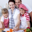 Family cutting colourful vegetables in kitchen — Stock Photo #10826249