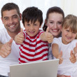 Family at home using a laptop with thumbs up — Stock Photo #10826258