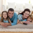Smiling family on floor in living-room — Stock Photo #10826260