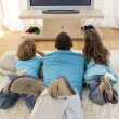 Family on floor in living-room watching television — Stock Photo