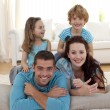 Stock Photo: Parents, daughter and son on floor in living-room