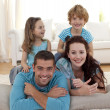 Parents, daughter and son on floor in living-room — Stock Photo