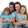 Family sitting on sofa together — Stock Photo