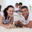 Happy couple playing chess on floor in living-room — Stock Photo