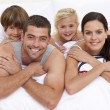 Happy family playing in parent's bed — Stock Photo #10826290