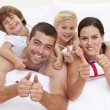 Family playing in bed with thumbs up — Stock Photo