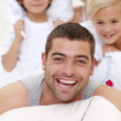 Family having a pillow fight in bed — Stock Photo