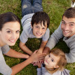 Young Parents and kids lying on garden with hands together — Stock Photo