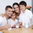 Happy family eating biscuits and drinking milk — Stockfoto