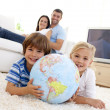 Children playing with a terrestrial globe at home — Stock Photo