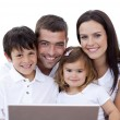 Portrait of young family using a laptop at home - Stock Photo
