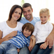 Smiling young family sitting on sofa — Stock Photo