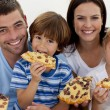 Stock Photo: Portrait of family eating pizzin living-room