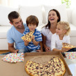 parents et enfants de manger la pizza dans le salon — Photo
