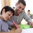 Stock Photo: Father helping his son doing homework