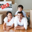 Stock Photo: Family on the floor smiling at the camera after buying house