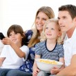 图库照片: Smiling family watching film at television