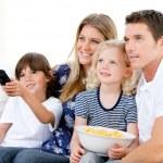 Улыбаясь семьи, смотреть фильм на телевидении — Стоковое фото