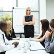 Attractive businesswoman in a meeting with folded arms — Stock Photo
