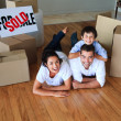 Family moving house on floor smiling at the camera — Stock Photo #10826509